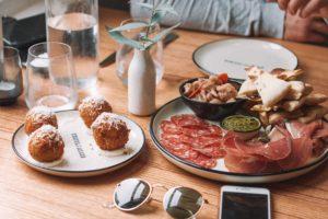 Une assiette de tapas de charcuterie posée sur une table en bois.