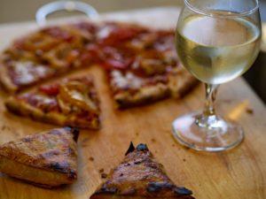 Un verre de vin blanc à coté d'une pizza.