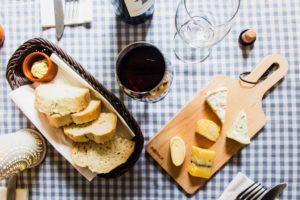 Un verre de vin rouge et une planche de fromage sur une table.